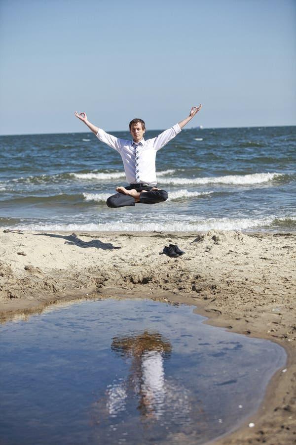 Der kaukasische Mann in den Lotos stellt Legetiere über dem Strand lizenzfreies stockfoto