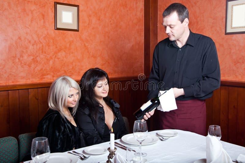 Der Kellner bietet Weinbesucher an lizenzfreie stockfotos
