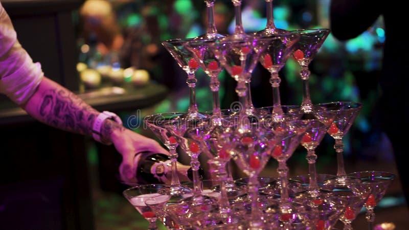 Der Kellner füllte Champagnerbrunnenpyramide von Gläsern Flasche Champagner, der in eine Glaspyramide ausgelaufen wird Leute lizenzfreie stockfotografie