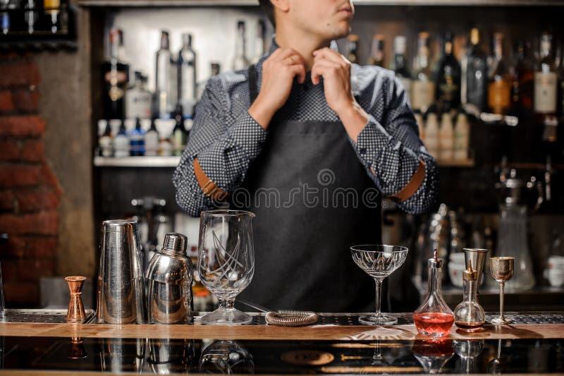 Der Kellner, der hinter dem Tresen steht, widersprechen mit Barutensilien stockbilder