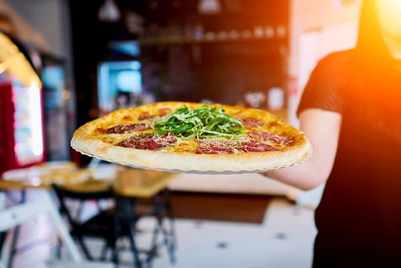 Der Kellner trägt die Pizza zum Kunden lizenzfreie stockfotos