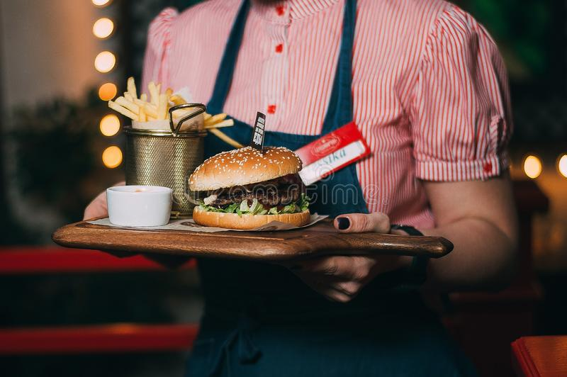 Der Kellner tr?gt einen Burger stockbild
