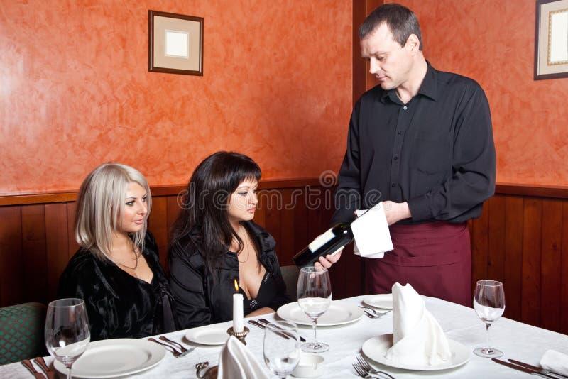 Der Kellner zeigt eine Flasche Wein stockbild