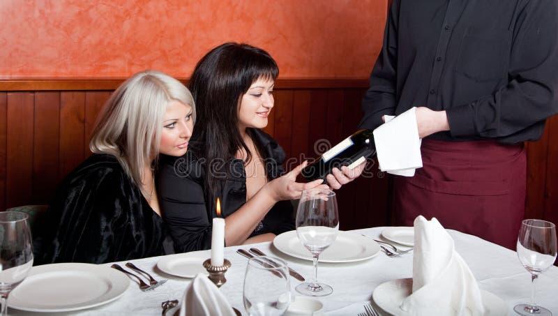 Der Kellner zeigt eine Flasche Wein stockfotos