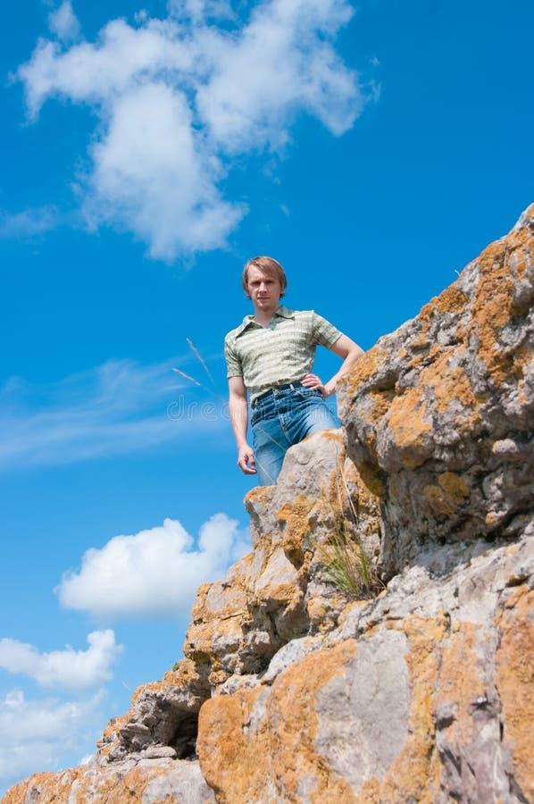 Der Kerl auf einem Felsen lizenzfreie stockfotos