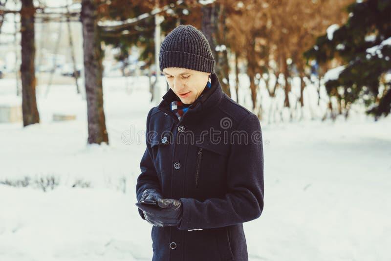 Der Kerl betrachtet das Telefon im Winter lizenzfreies stockbild