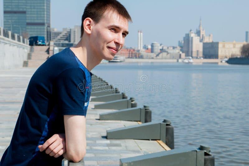 Der Kerl in den blauen Hemdständen, lehnend auf dem Geländer auf der Ufergegend des Flusses und schielen vom hellen Sonnenschein lizenzfreie stockfotografie