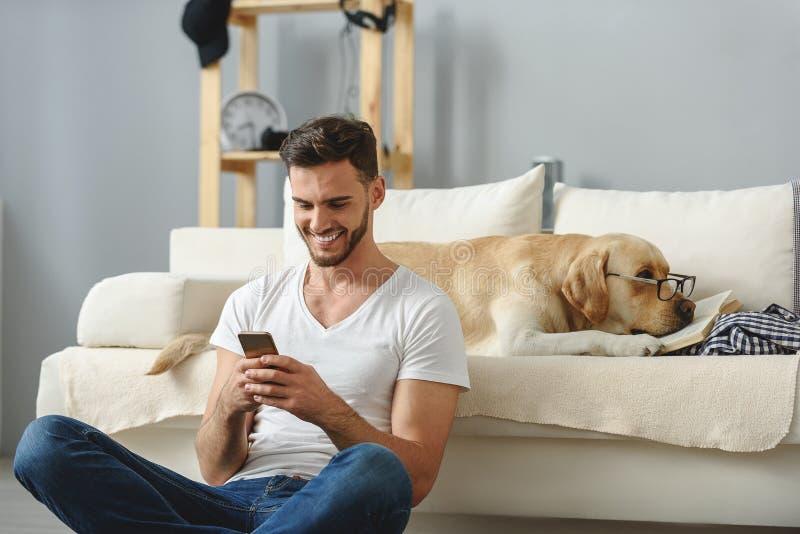 Der Kerl, der auf Smartphone spielt und bemerkt nicht seinen Hund lizenzfreie stockfotos