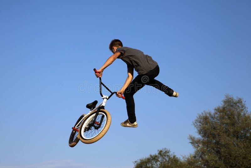 Der Kerl führt einen Sprung auf einem Bremsungsfahrrad durch stockfotos