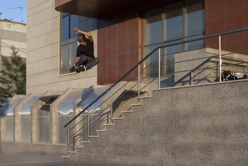 Der Kerl fliegt durch die Leiter, nachdem er auf einen Inline-Rollschuh gesprungen ist lizenzfreie stockbilder