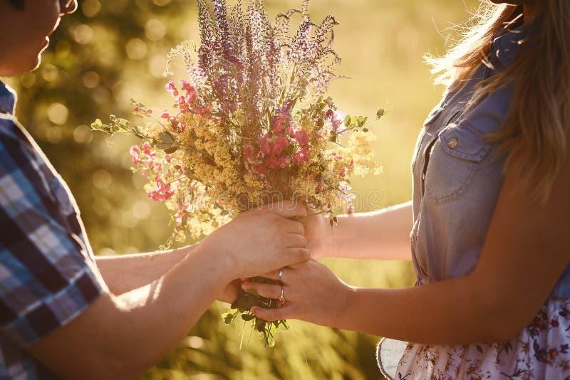 Der Kerl gibt dem Mädchen schöne wilde Blumen draußen im Sommer stockbild