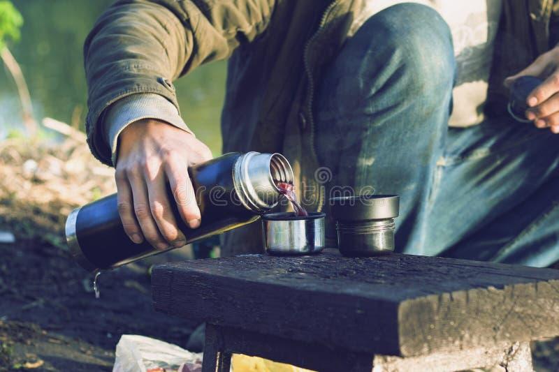 Der Kerl gießt Beerentee von einer Thermosflasche in der Natur Das Konzept Erholung der im Freien lizenzfreies stockfoto