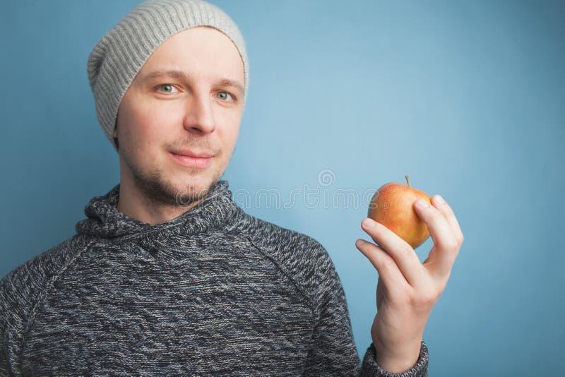 Der Kerl im Hut, der in der Hand Apple gegen einen blauen Hintergrund hält lizenzfreies stockbild