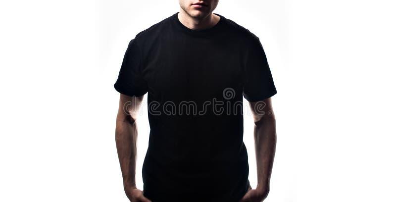 Der Kerl im leeren schwarzen T-Shirt, Stand, oben auf einem weißen Hintergrund, Spott, freier Raum, Logo, Design, lächelnd Schabl lizenzfreie stockfotografie