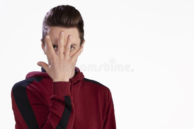 Der Kerl im Studio, das sein Gesicht mit seiner Hand bedeckt stockbilder