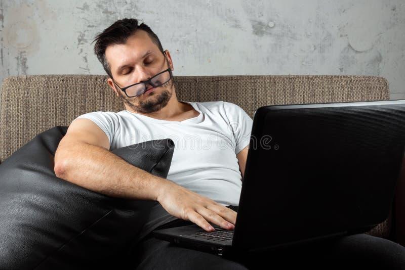 Der Kerl im wei?en Hemd, das auf der Couch sitzt, schlief bei der Arbeit ?ber einen Laptop ein Das Konzept der Tr?gheit, Apathie lizenzfreies stockbild