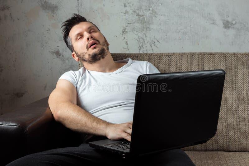 Der Kerl im wei?en Hemd, das auf der Couch sitzt, schlief bei der Arbeit ?ber einen Laptop ein Das Konzept der Tr?gheit, Apathie lizenzfreie stockfotos