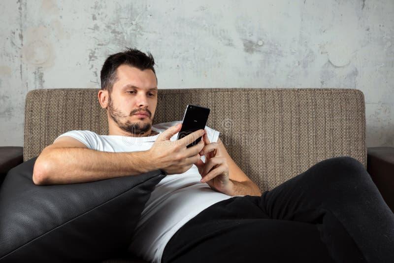 Der Kerl im wei?en Hemd liegt auf der Couch und sitzt im Telefon Das Konzept der Tr?gheit, Apathie lizenzfreie stockbilder