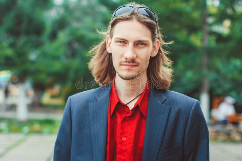 Der Kerl in der Jacke mit dem langen Haar stockfoto