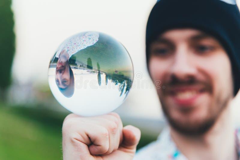 Der Kerl lernt, einen transparenten Ball zu jonglieren stockfotografie