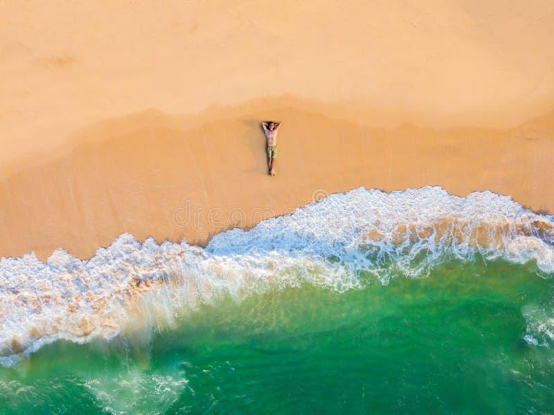 Der Kerl liegt auf einem sandigen Strand auf einer Tropeninsel Brummenansicht stockbild