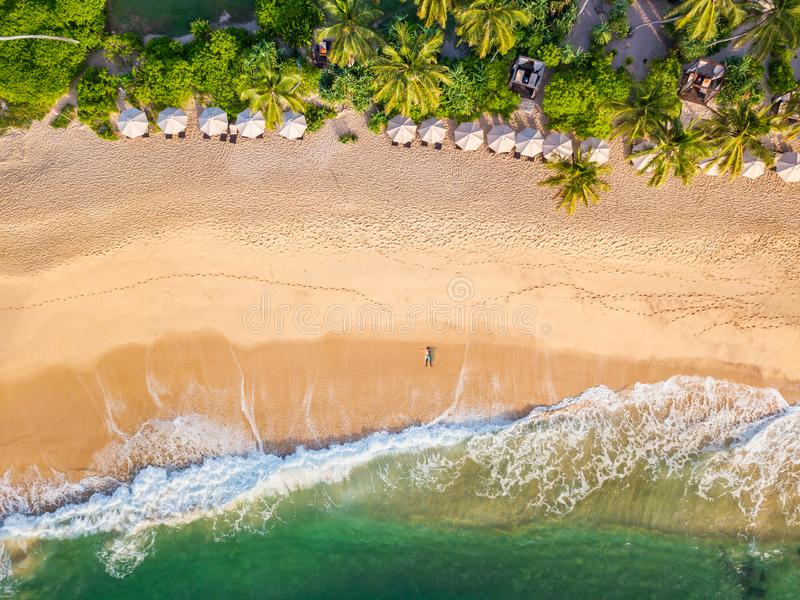 Der Kerl liegt auf einem sandigen Strand auf einer Tropeninsel Brummenansicht lizenzfreie stockfotografie