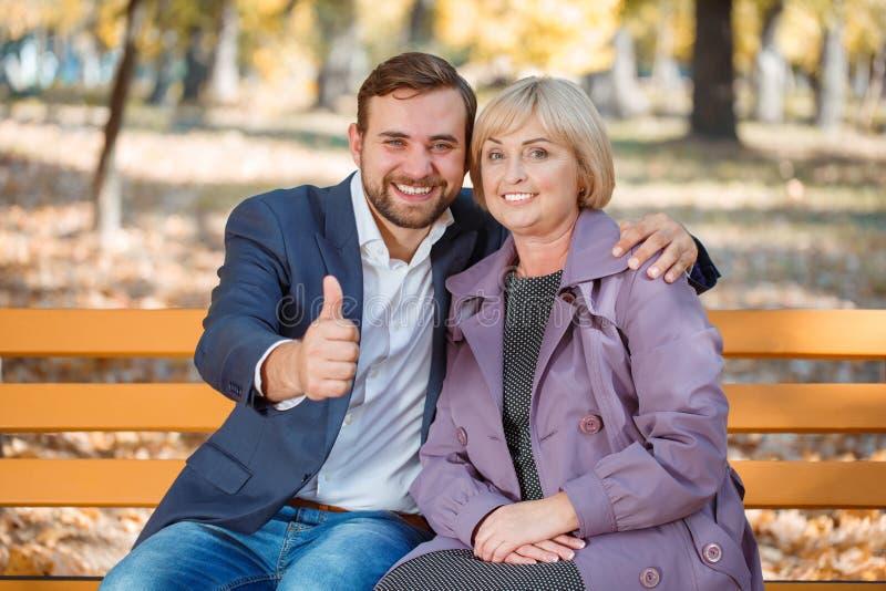 Der Kerl mit einem Lächeln umarmt meine Mutter in einem Herbstpark auf einer Bank lizenzfreie stockfotografie