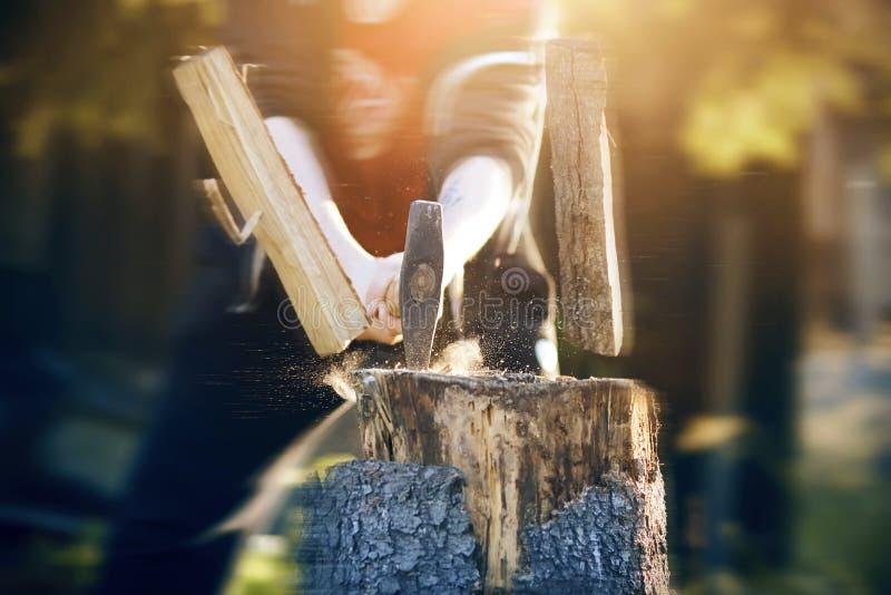 Der Kerl schneidet kräftig Klotz mit einer scharfen Axt stockfotos