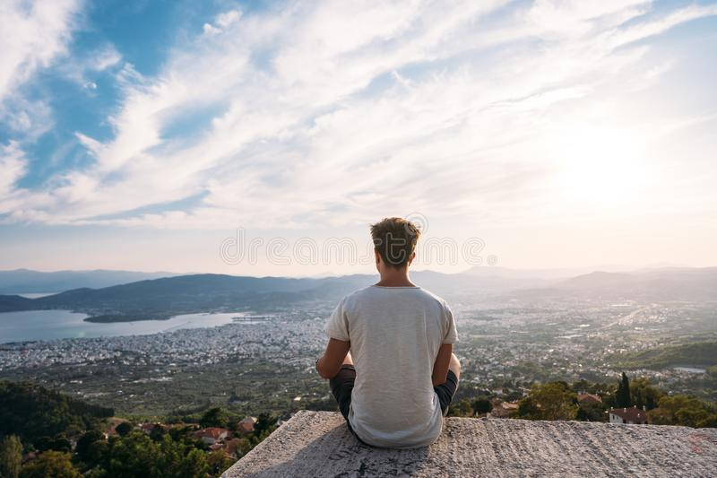 Der Kerl sitzt am Rand des Dachs, im Hintergrund ist die Küstenstadt lizenzfreie stockfotos