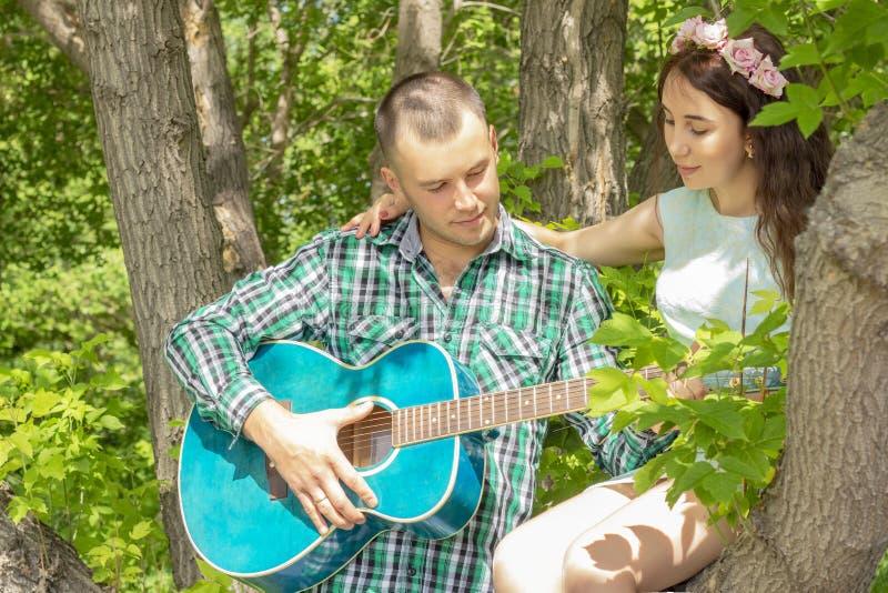 Der Kerl spielt Gitarre zu seiner Freundin Romantische Sitzung M?dchen, das in einem Baum sitzt lizenzfreies stockfoto