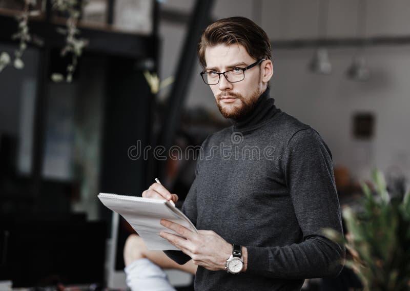Der Kerl, der in der zufälligen Büroartkleidung gekleidet wird, macht Anmerkungen in einem Notizbuch im modernen Büro lizenzfreies stockfoto