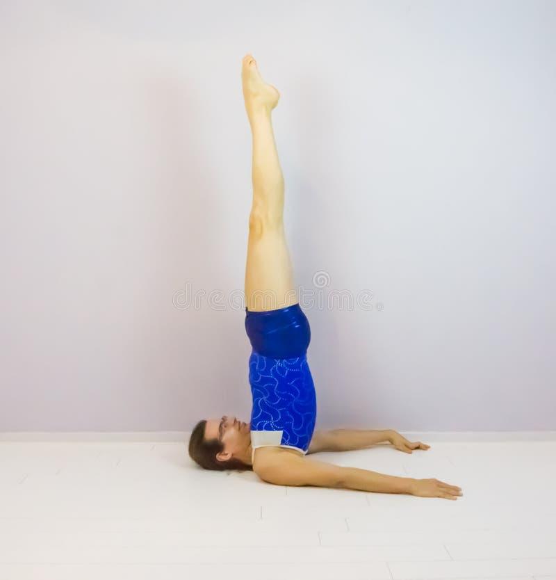 Der Kerzenhalter eine akrobatische Gymnastikfähigkeitsübung vorgeformt von einem jungen Transgendermädchen lizenzfreies stockbild