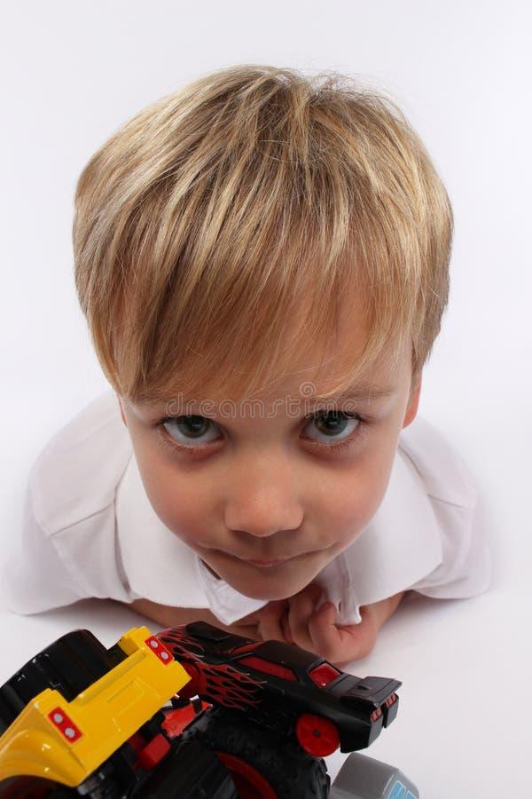 Der Kinderjunge, der dumme Gesichter macht und wünscht Sie spielen stockfoto