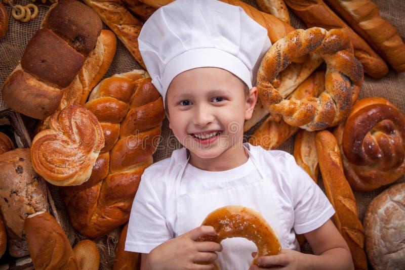 Der Kinderkoch, der oben gekleidet wird, liegt Bäcker viele Brötchen lizenzfreie stockfotografie