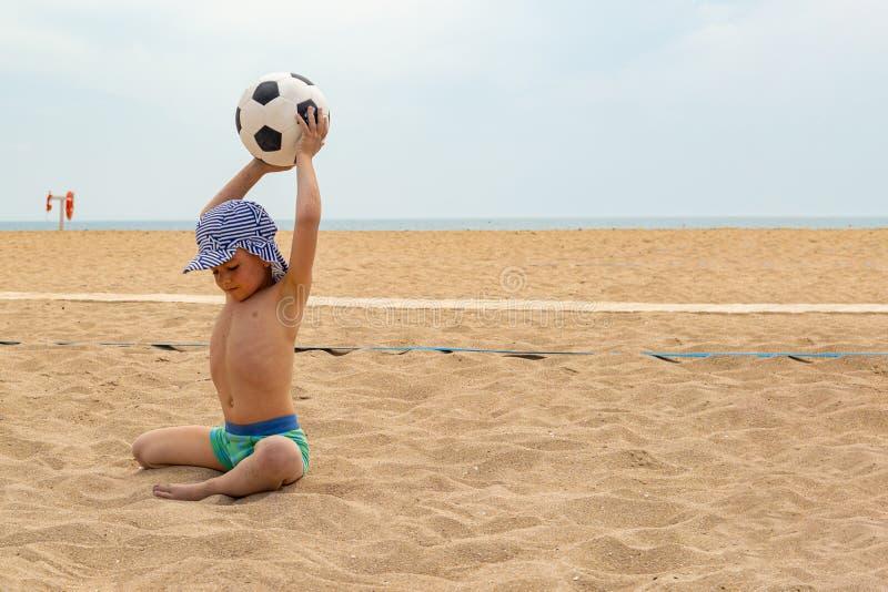 Der Kinderspielfußball auf dem Strand lizenzfreies stockbild