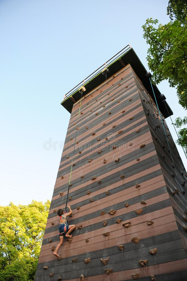 Der kleine athletische Junge, der auf Felsenwand des hohen Turms draußen klettert, tragen copyspace zur Schau lizenzfreie stockfotografie