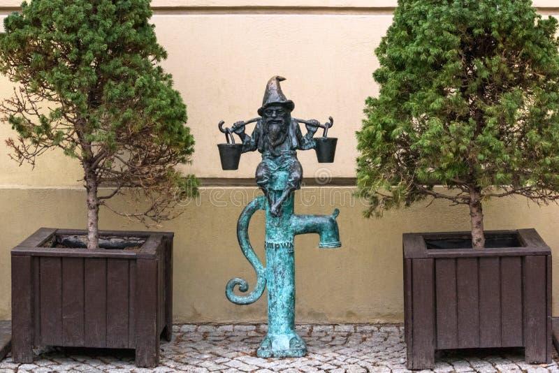 Der kleine Bronzestatuengnom namentlich - Wodziarz, Gnom mit Eimern auf Wassersäule lizenzfreie stockfotos