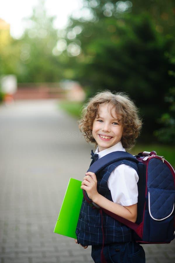 Der kleine gelockte behaarte Junge steht im Hof der Schule lizenzfreie stockbilder