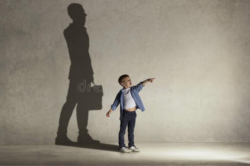 Der kleine Junge, der über Geschäftsmannberuf träumt stockfoto