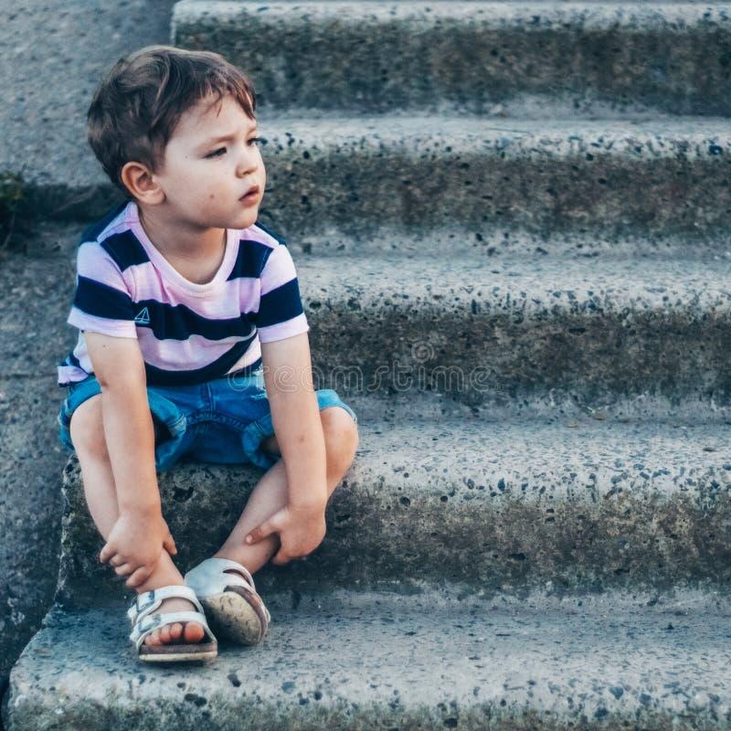 Der kleine Junge, der auf Steinschritten sitzt, schaut unten, nachdenklicher Blick und seine Arme draußen halten Raum für Text -J lizenzfreie stockfotografie