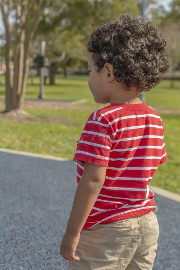 Der kleine Junge betrachtet weg dem Park stockfoto