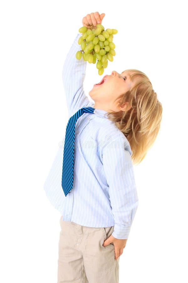 Der kleine Junge, der grüne Trauben anhält und essen lizenzfreies stockbild