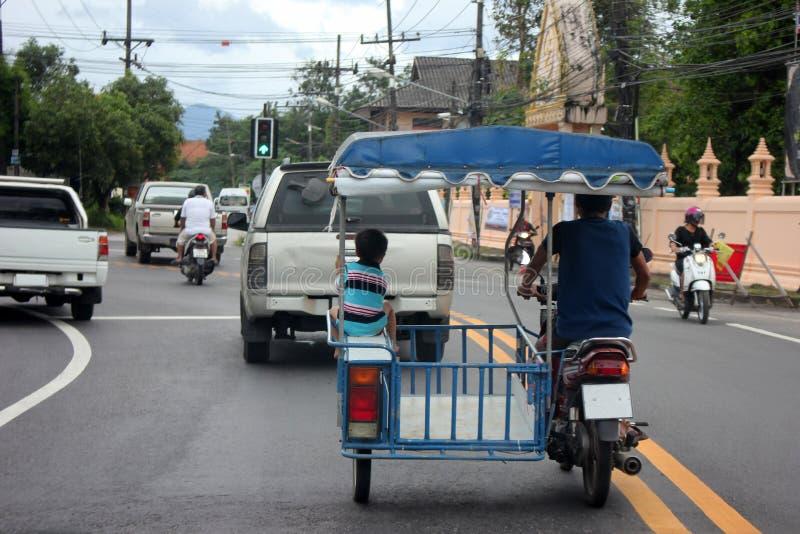 Der kleine Junge, der im Einheimischen sitzt, änderte Motorrad auf den Straßen lizenzfreie stockbilder