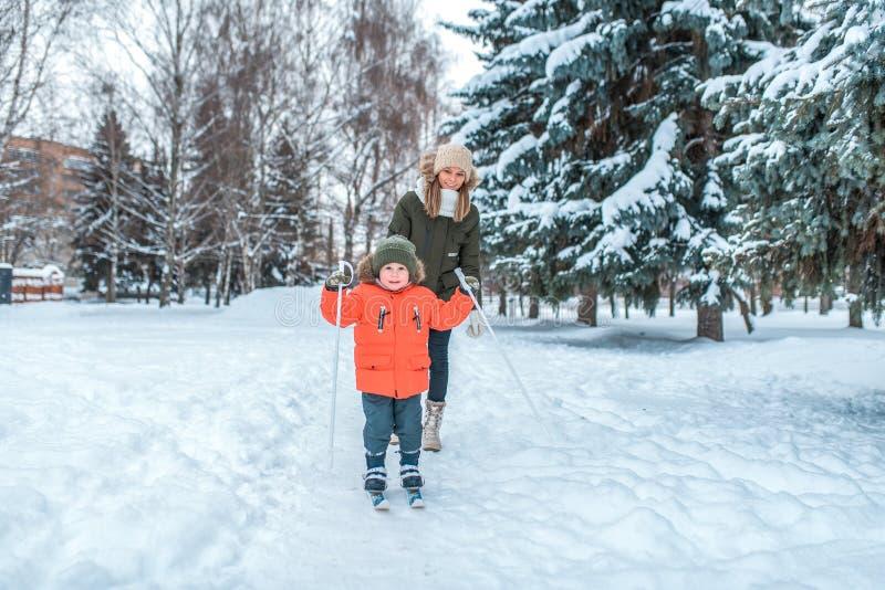 Der kleine Junge 3-5 Jahre alt, Ski fahrend im Winter in einer schneebedeckten jungen Mutter des Wald A geht in die Rückseite Akt stockfotos