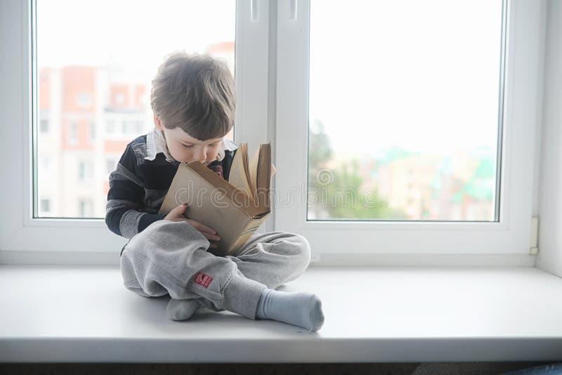Der kleine Junge liest ein Buch Das Kind sitzt am Fenster a stockfotos
