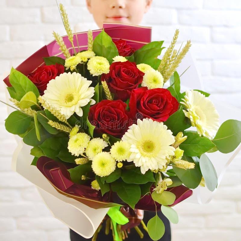 Der kleine Junge mit einem schönen Blumenstrauß von Blumen für seine Mutter lizenzfreie stockfotos