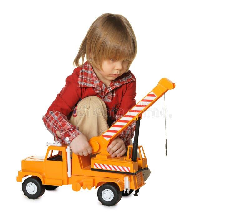 Der kleine Junge mit einem Spielzeug - ein LKW-Kran lizenzfreie stockfotografie