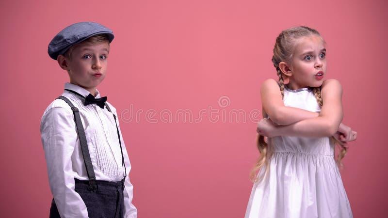 Der kleine Mann, der die Kamera entsetzt wird mit Freundinbeanstandung untersucht, Kinder streiten lizenzfreies stockfoto