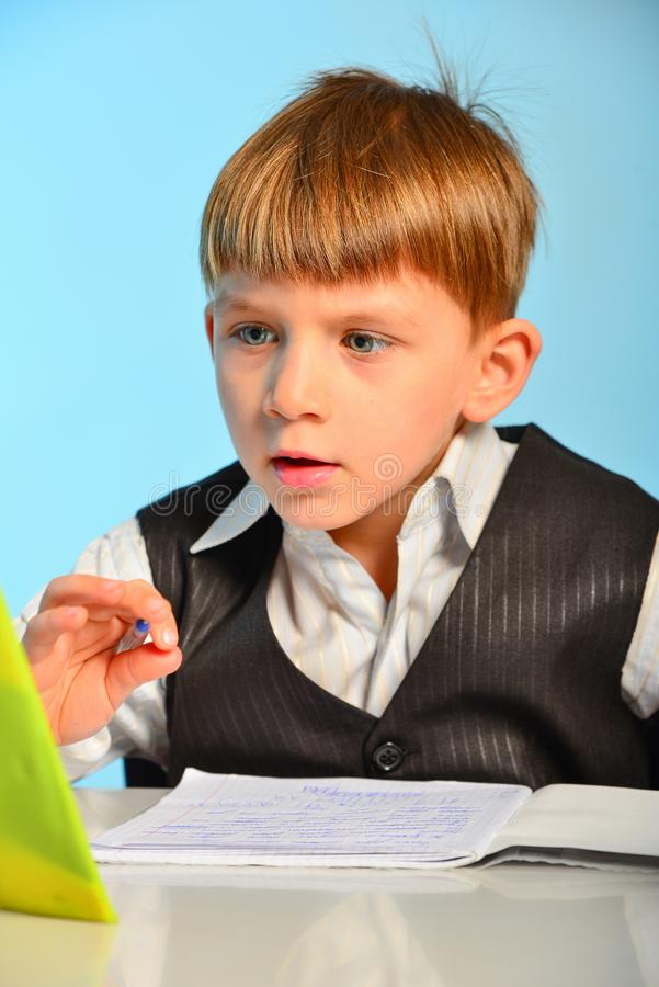 Der kleine Schüler mit Überraschung liest die Bedingung der Aufgabe, tut die Lektionen für die Schule stockfotografie