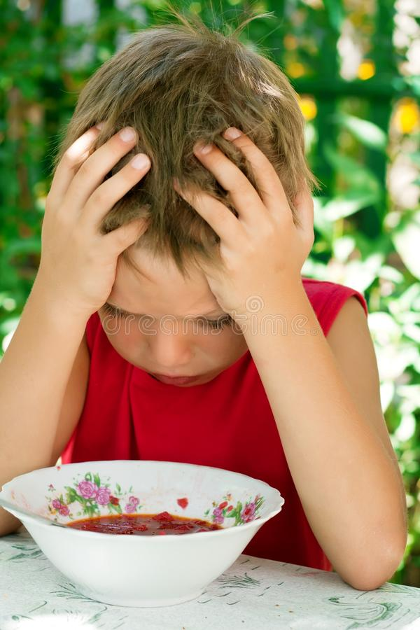 Der kleine traurige Junge isst Suppe lizenzfreies stockbild
